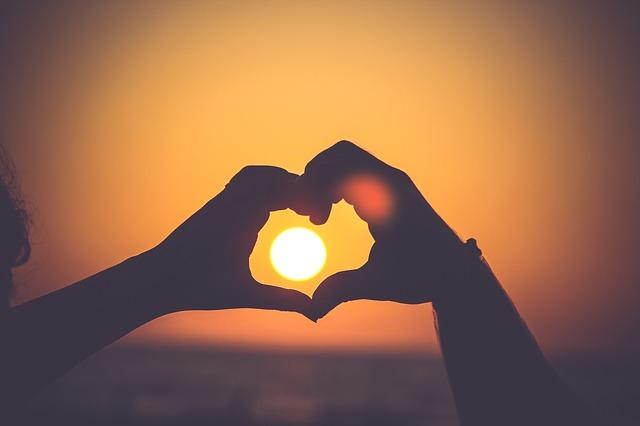 Dlaně vytvářející tvar srdce, vprostřed nich září slunce